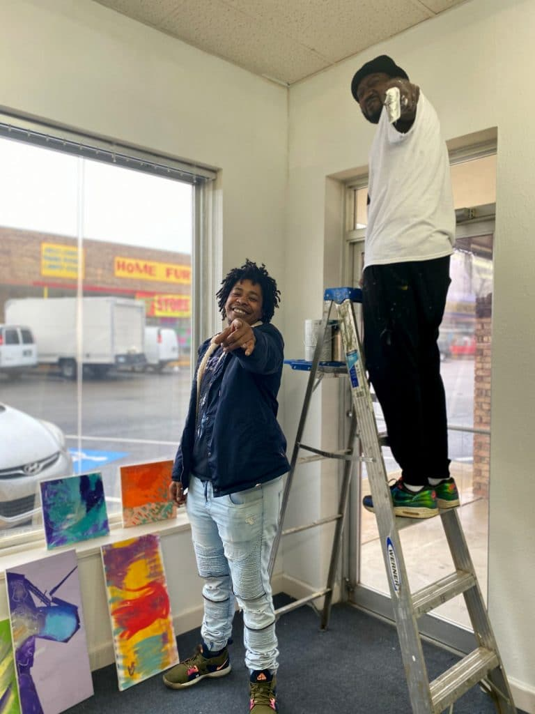 DoubleBlind: Transgender Rapper and Military Vet poses with friend on a ladder in front of his psychedelic paintings.