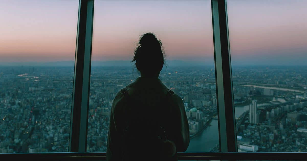Doubleblind: Silhoutte of a woman looking out of a window at a cityscape. In this article, Doubleblind explains that COVID-19 isn't just a medical crisis - it's an existential one.
