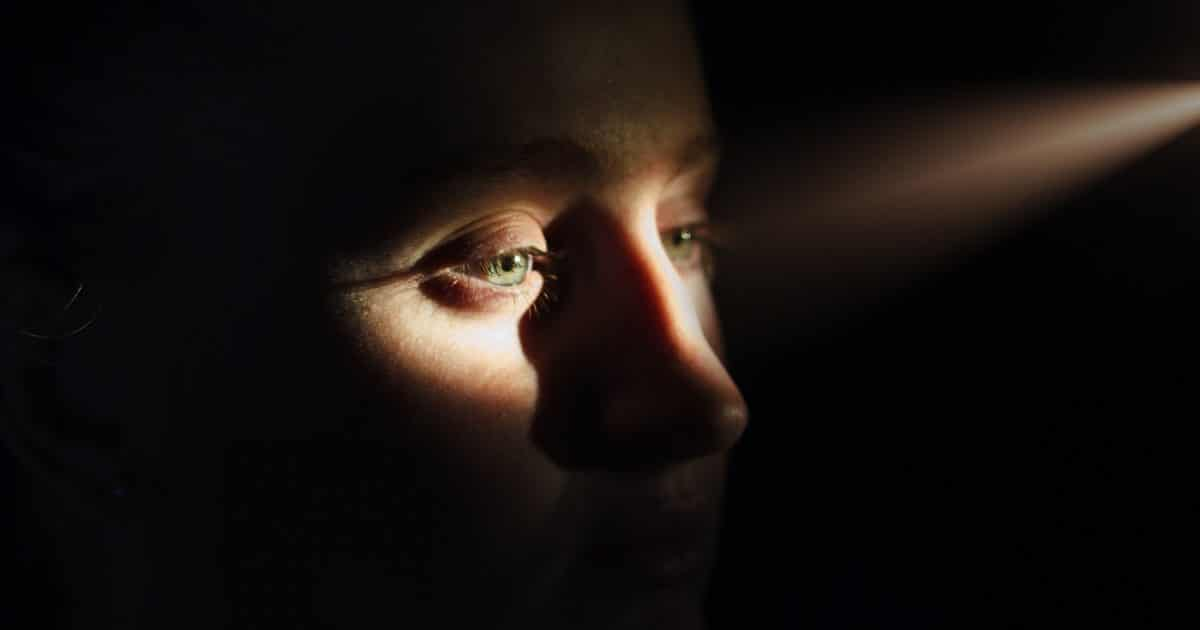 Doubleblind: Woman in darkness has a sliver of light fall on her eyes and nose. In this article, Doubleblind explores how ketamine, the psychedelic painkiller, could potentially halt the opioid crisis.