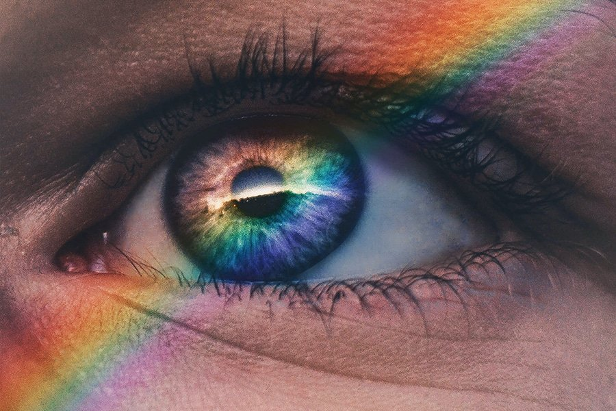 DoubleBlind: Image of eye looking out with rainbow light shining on it. In this article, DoubleBlind explore LGBTQI psychedelic researchers.