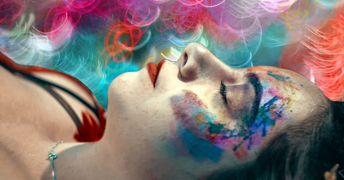 DoubleBlind: Woman with eyes closed and neon lights above her. In this article, DoubleBlind explores 4-Acetoxy-DMT, a.k.a synthetic shrooms.