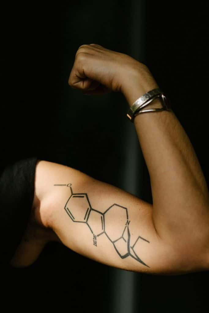 DoubleBlind: Image ibogaine molecular structure tattooed on arm. In this article, DoubleBlind explores using ibogaine to treat opioid addiction.
