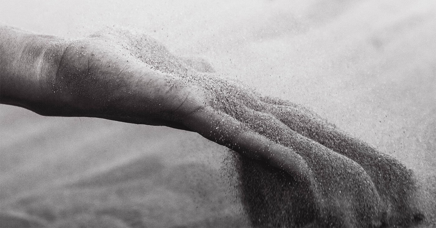 DoubleBlind: Black and white image of hand releasing sand.