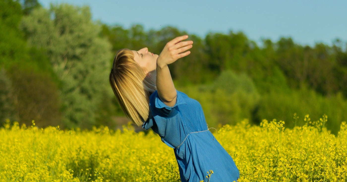 DoubleBlind: Image of woman falling backwards in field of yellow flowers. In this article, DoubleBlind explores the use of psychedelics for treating physical pain.