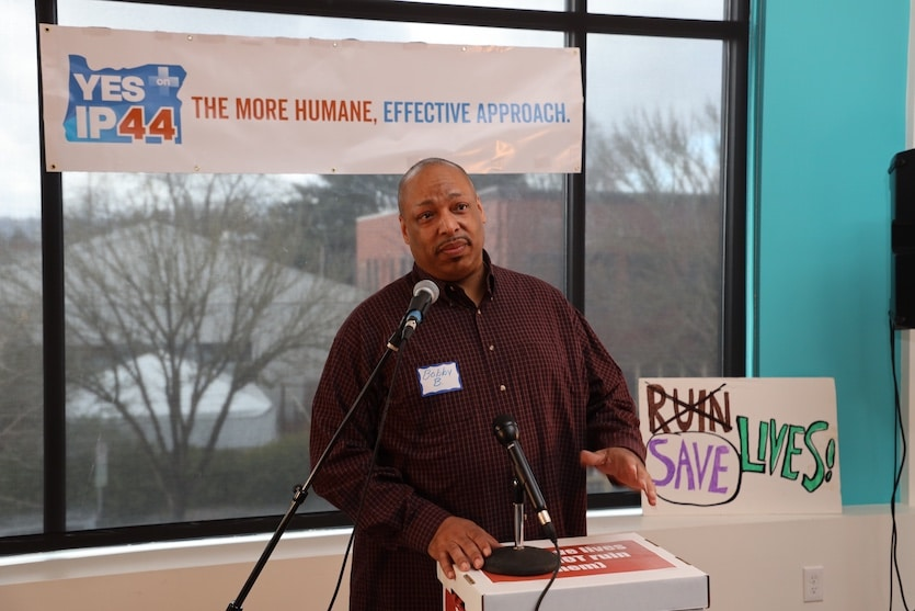 DoubleBlind: Man speaking at podium at campaign event. In this article, DoubleBlind discusses Oregon's Measure 110 to decriminalize small amounts of all drugs.