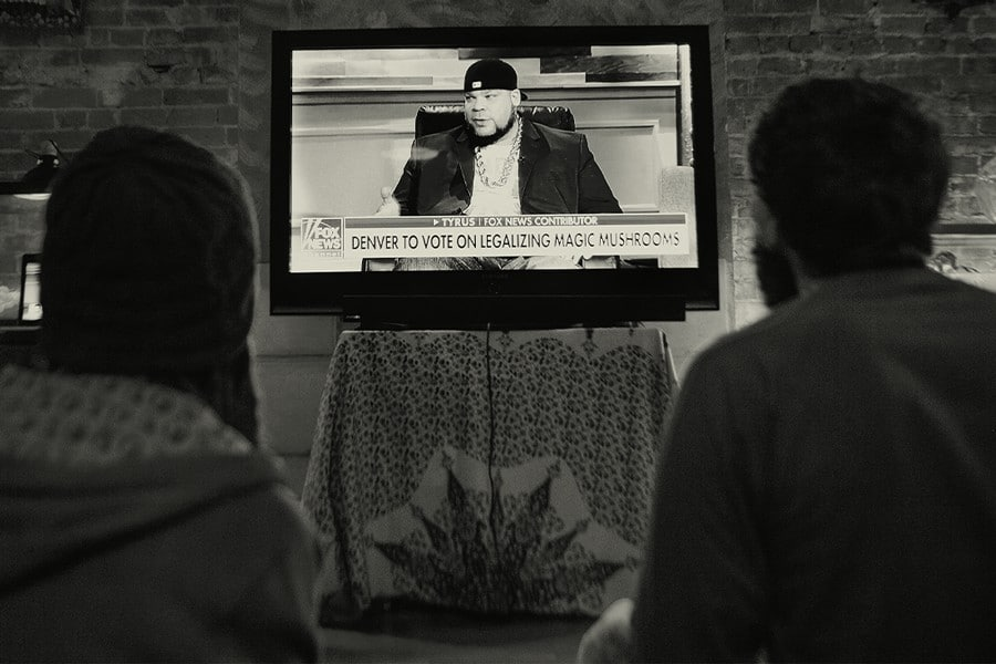 DoubleBlind: Decriminalize Denver activists watch a. major news network broadcast on their campaign.