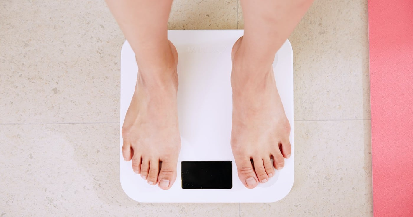 DoubleBlind: Image of feet on scale. In this article, DoubleBlind explores the potential for psychedelics to heal eating disorders.