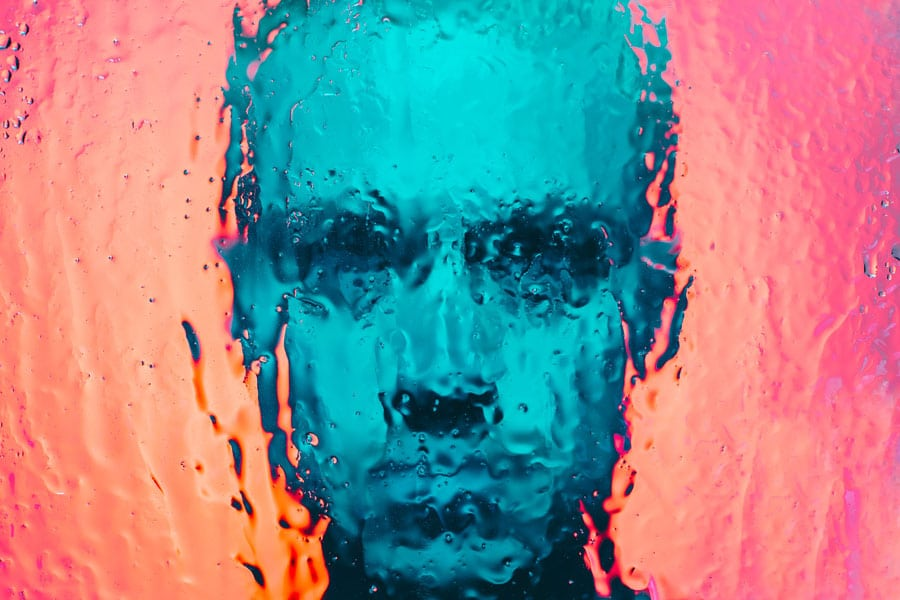 DoubleBlind: Image of man behind wet glass. In this article, DoubleBlind explores what removing the hallucinations from psychedelics means for psychotherapy.