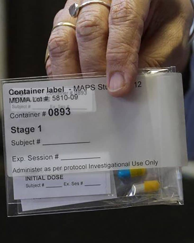 DoubleBlind: Image of hand holding MDMA capsules in MAPS MDMA-assisted psychotherapy trials.