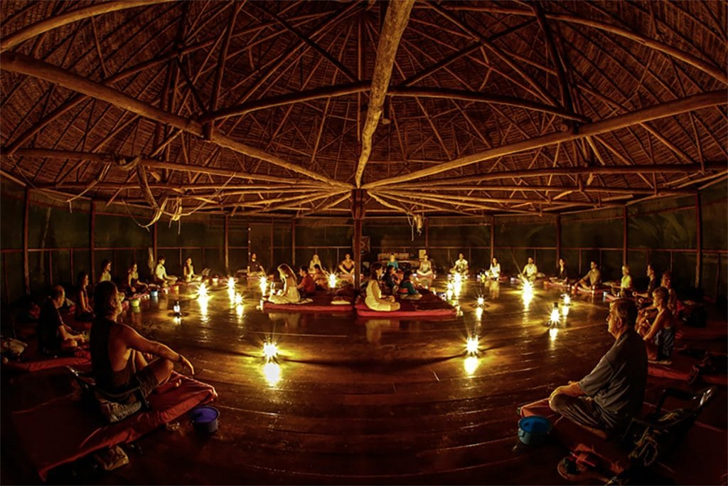 Group of people sitting on the floor in a circle in a dimly lit hut for an ayahuasca ceremony