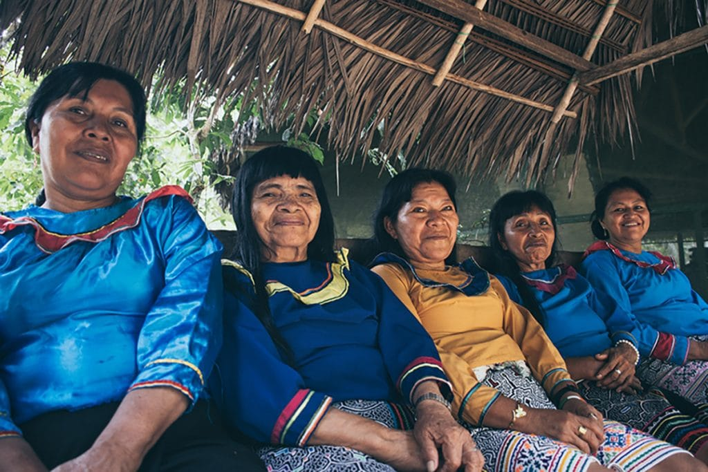 5 female Shipibo healers sitting in a row underneath a thatched roof
